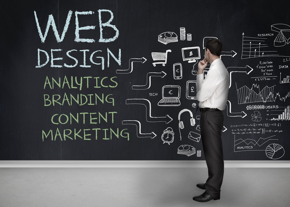 Businessman standing in front of a chalkboard with web design terms written on it.jpeg